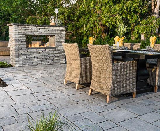unilock thornbury pavers in almond grove with stone outdoor fireplace