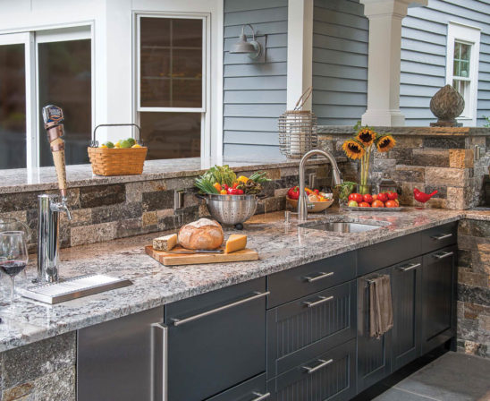 brown jordan outdoor kitchen with sink, keg line, and marble countertops