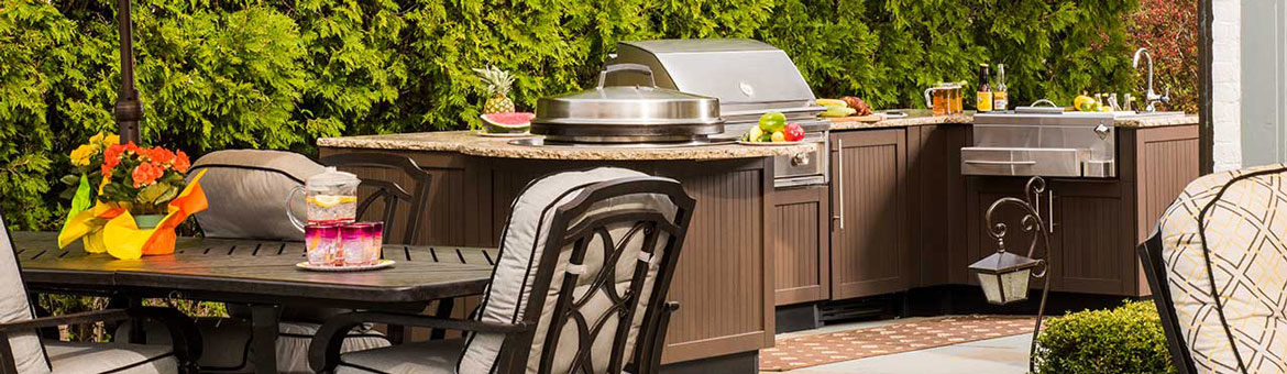 brown jordan outdoor kitchen with built in grill and outdoor bar on thermalled bluestone flagstone patio with cast aluminum outdoor dining furniture and yellow patio umbrella