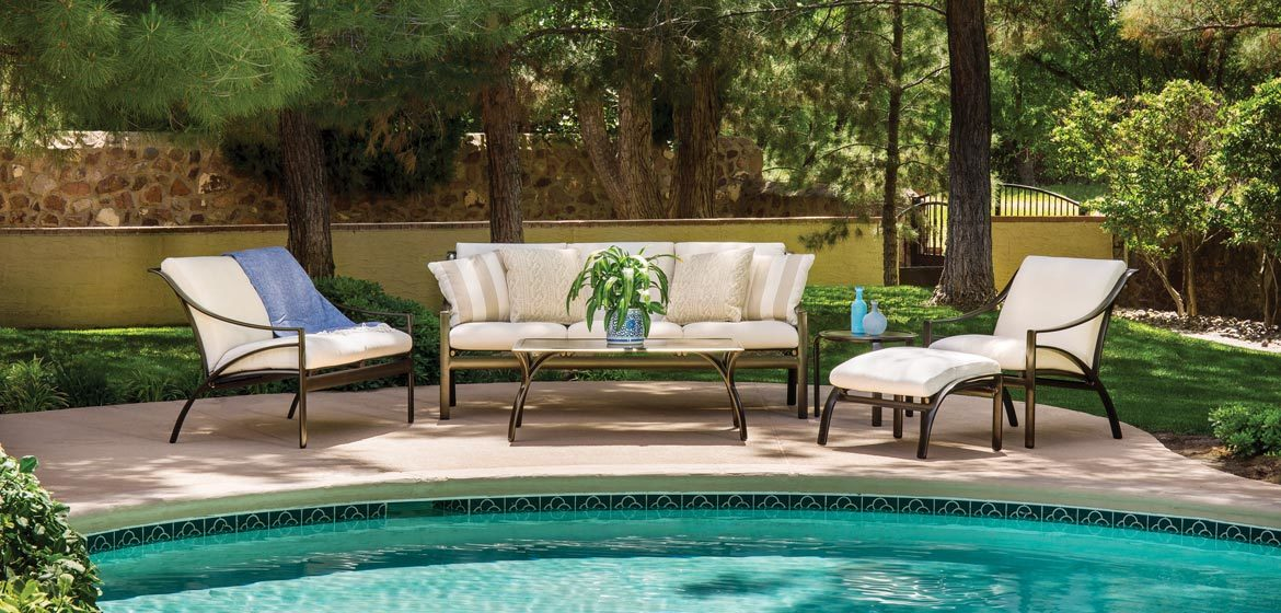 Pasadena outdoor cushion seating from brown jordan with sofa, lounge chair, ottoman and coffee table on a pool deck in the woods with a beautiful stone wall in the background