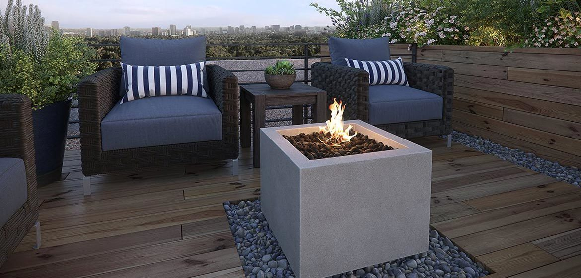 eldorado outdoor bloc fire bowl single on wooden deck with mexican beach pebbles and wicker outdoor furniture
