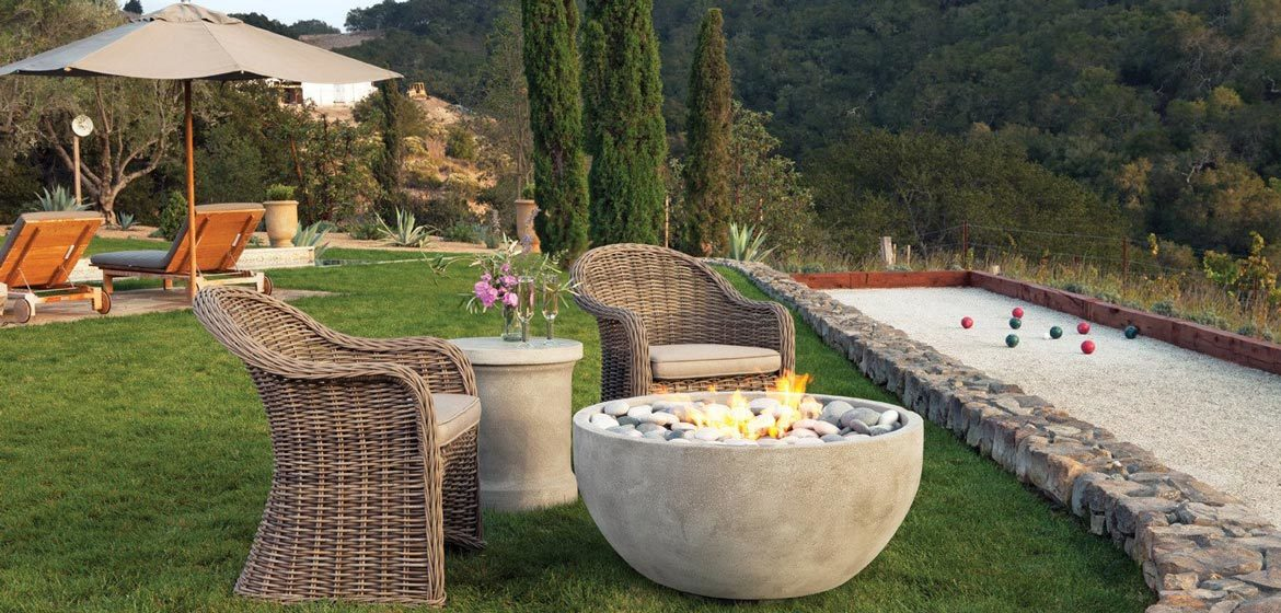 eldorado outdoor infinite fire bowl near bocce court with wicker seating in beautiful mountain setting