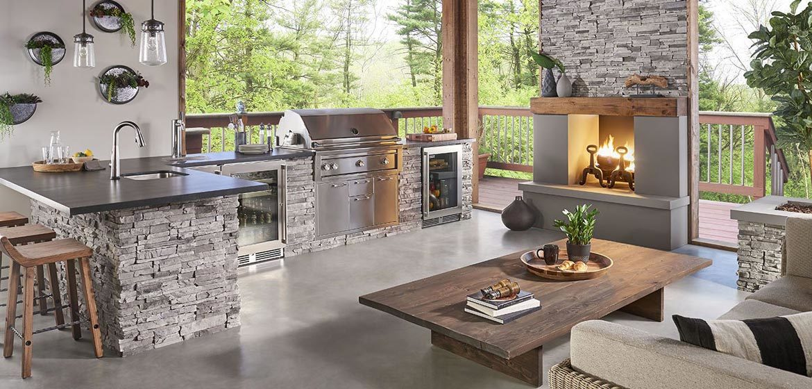eldorado outdoor kitchen with grey stackstone and built in grill and stainless steel beverage refrigerator
