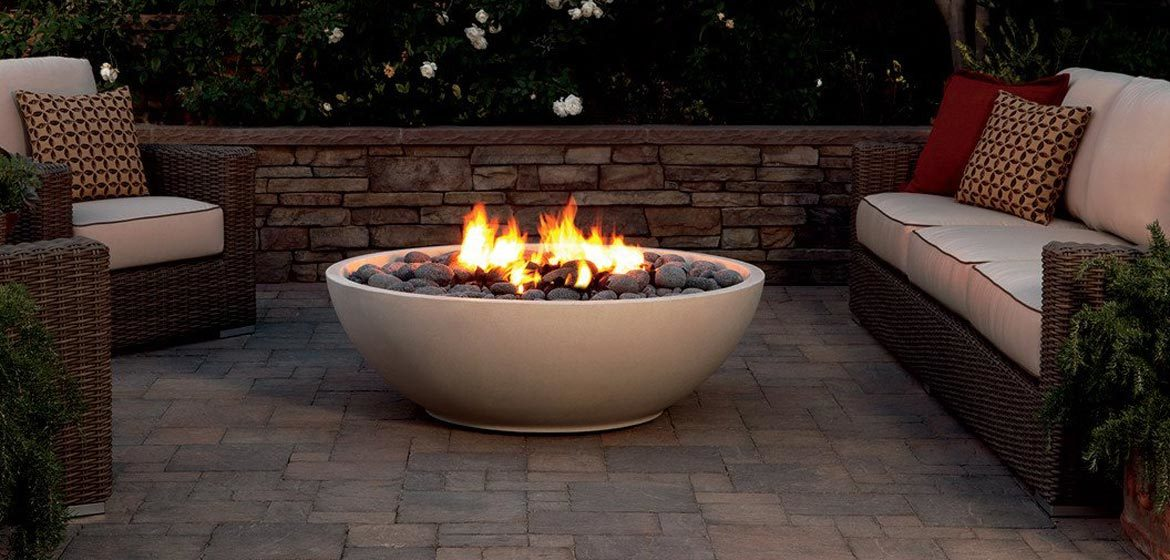 eldorado outdoor mezzaluna fire bowl on concrete paver patio with wicker furniture
