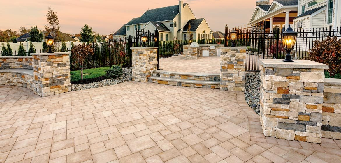 EP Henry's Bristol Stone Smooth concrete paver patio with Cast Veneer Stone columns and an outdoor kitchen
