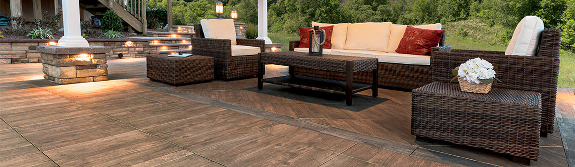 ep henry lastra porcelain landscape tile axi brown chestnut patio with wicker outdoor sofa and lounge chair and cast stone wall columns