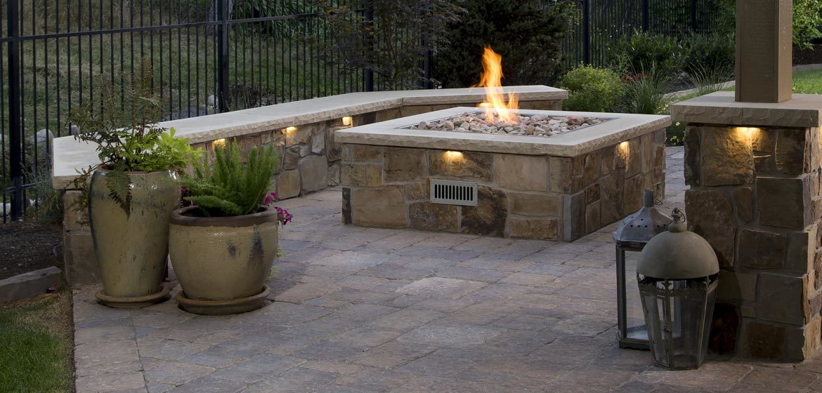 firegear outdoors propane or natural gas burning spur for square fire pits on concrete paver patio with natural thin stone veneer on seat walls and columns
