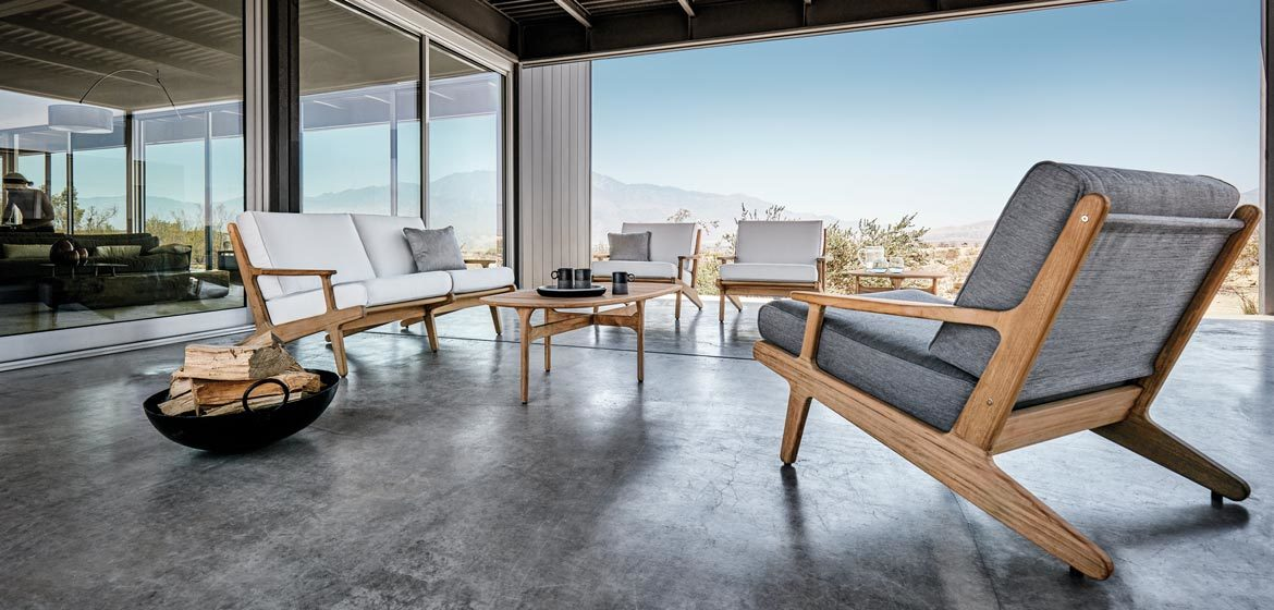 Bay teak outdoor sofa and lounge chairs by Gloster at a modern home on a stained and polished concrete patio