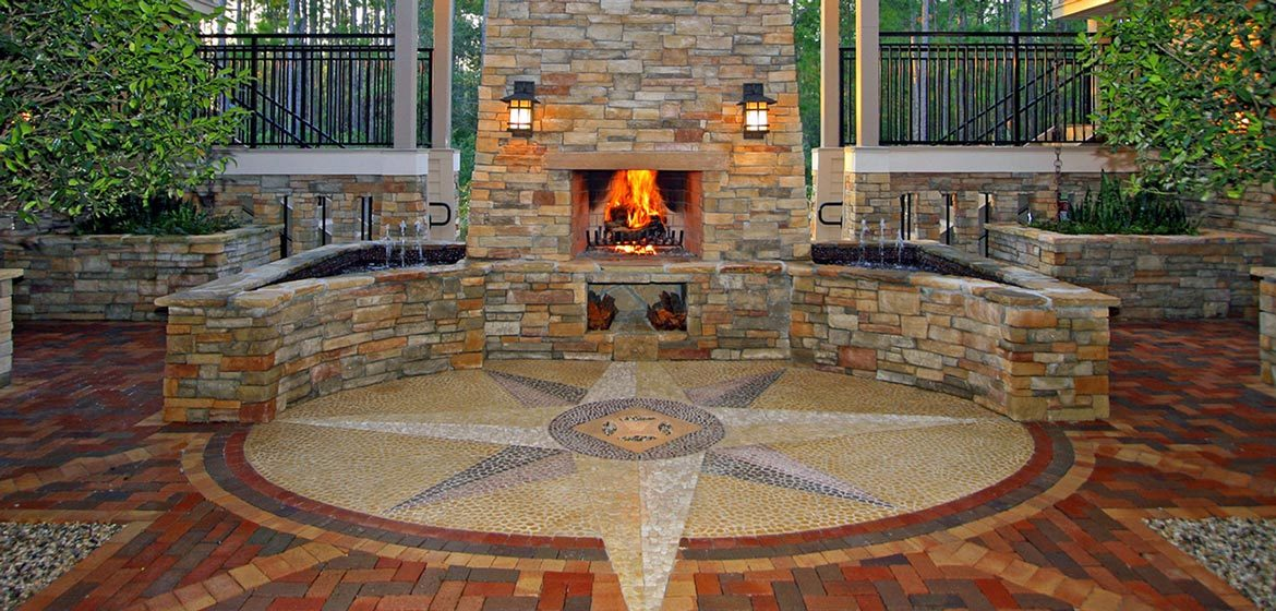 isokern outdoor fireplace with natural stone veneer exterior on brick paver patio with circular tile inlay and large star medallion