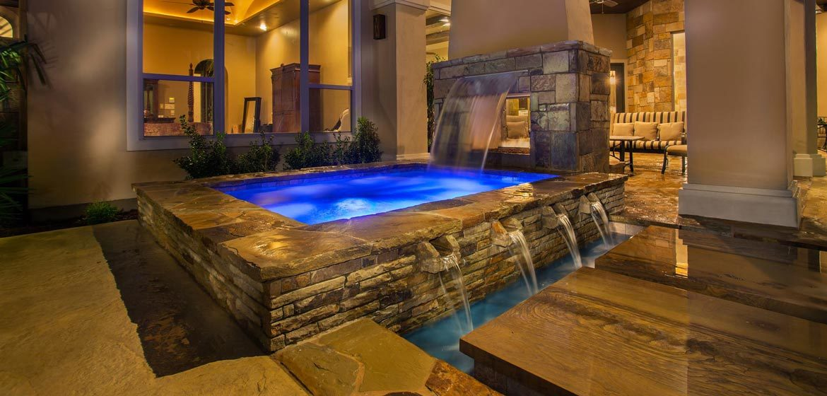 isokern see through outdoor fireplace interior view with adjacent waterfalls and polished brentwood countertop stone