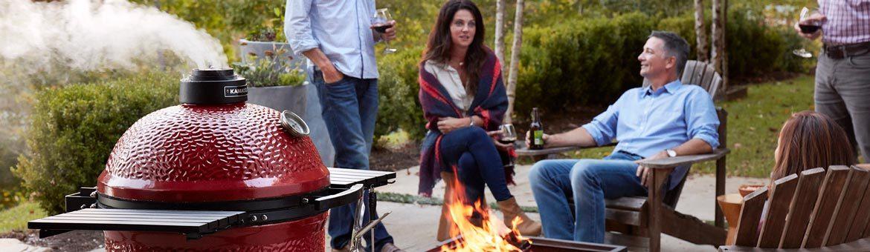 Folks relaxing around a Kamado Joe firepit.
