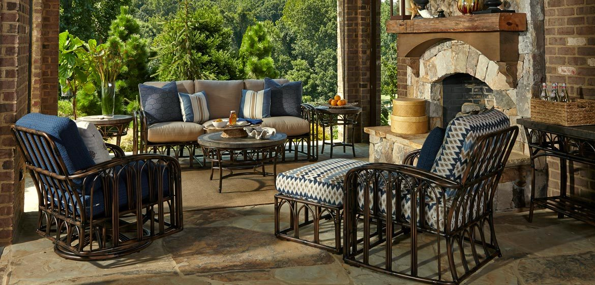 Klaussner Outdoor Capella rattan cushion seating on irregular flagstone patio with beautiful stone fireplace