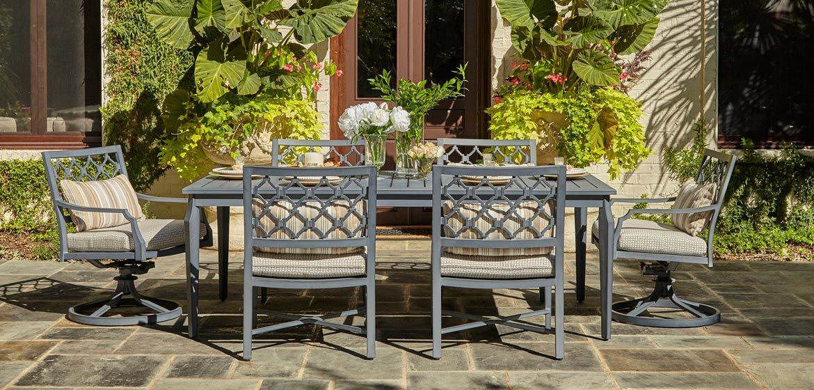 Klaussner Outdoor Mirage collection rectangular dining table with swivel rockers and side chairs on a flagstone patio in front of a painted brick home