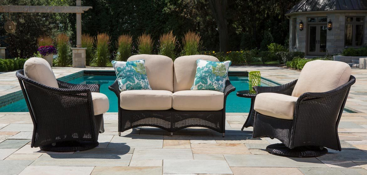 Lloyd Flanders Generations outdoor wicker cushion seating with love seat and swivel glider chairs on flagstone patio by a beautiful pool and pergola