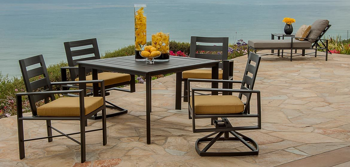 O W Lee Gios collection modern aluminum outdoor dining furniture on irregular flagstone patio by the ocean