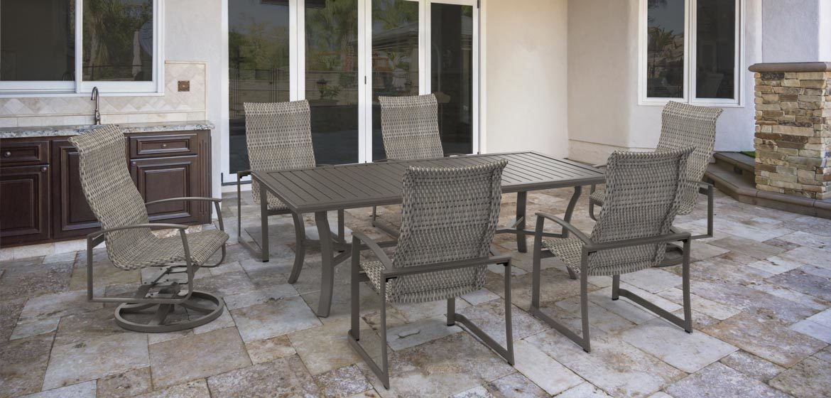 Tropitone's Mainsail Woven outdoor dining furniture on a travertine patio next to an outdoor kitchen
