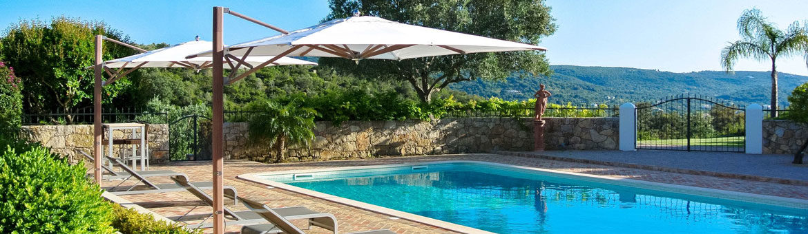 tuuci single cantilever umbrella on brick pool deck with sling chaise loung chairs