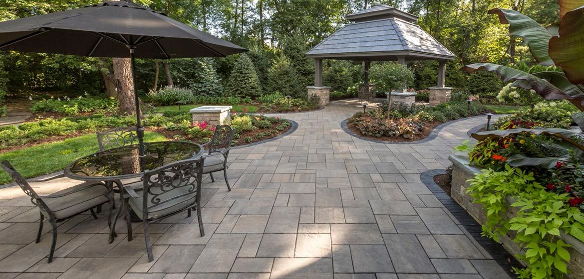 unilock beacon hill flagstone almond grove concrete paver patio with cast aluminum outdoor dining table and pergola