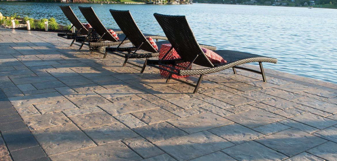 unilock beacon hill flagstone sierra concrete paver patio near lake with wicker chaise lounge chairs