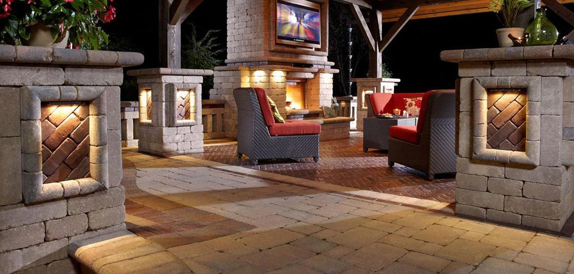 unilock brussels block concrete paver patio and outdoor room with copthorne border and brussels dimensional columns and landscape lighting and outdoor television
