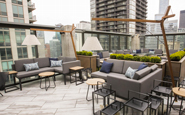 unilock delconca porcelain landscape tile on rooftop patio rooftop deck with contemporary outdoor sectional sofa and cantilever umbrella and outdoor lanterns