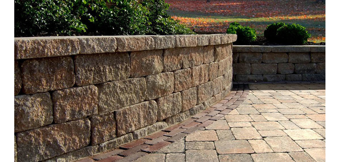 unilock estate wall seat wall and brussels block concrete paver patio with copthorne accent band