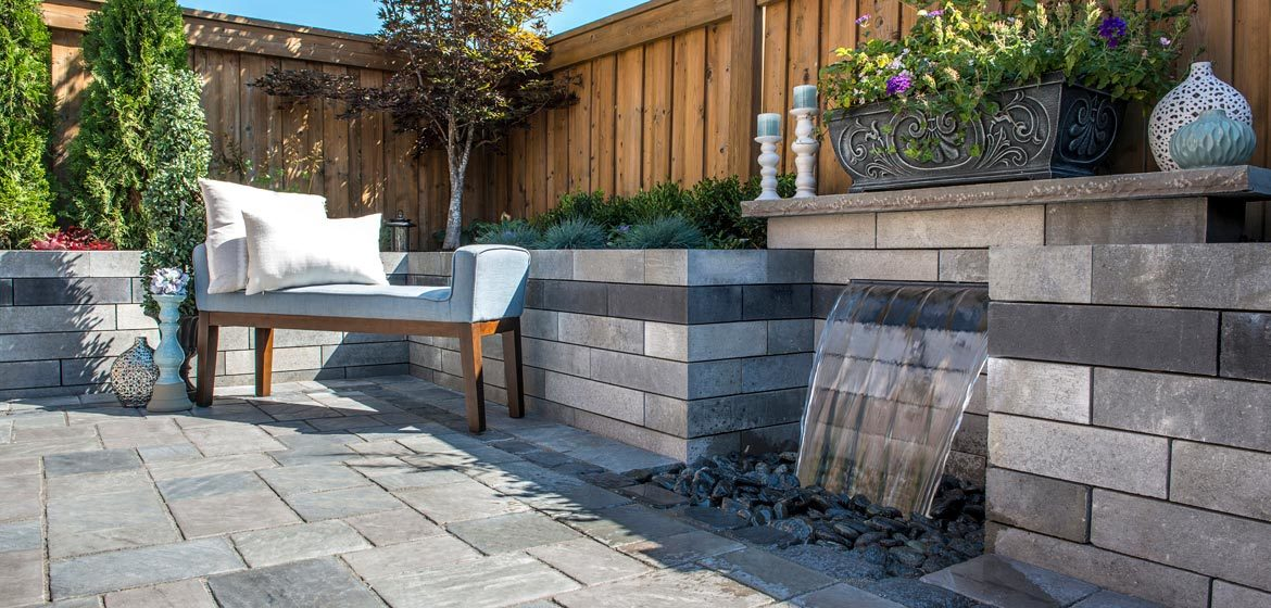 unilock richcliff dawn mist concrete paver patio with lineo retaining wall and wall fountain