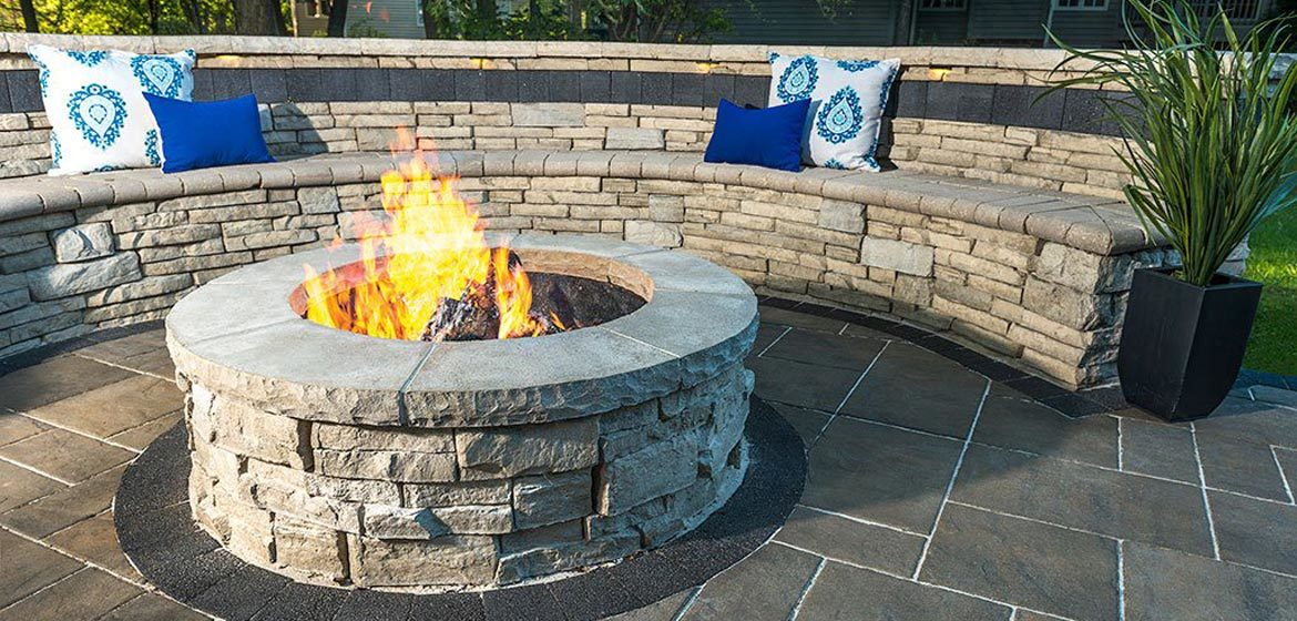 unilock rivercrest fire pit with rivercrest seating wall and colorful outdoor throw pillows