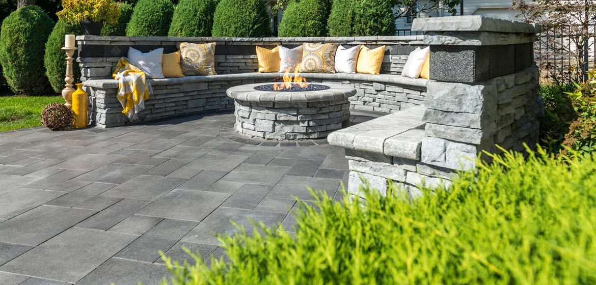 unilock umbriano concrete paver patio and rivercrest seat wall with back and gas outdoor fire pit