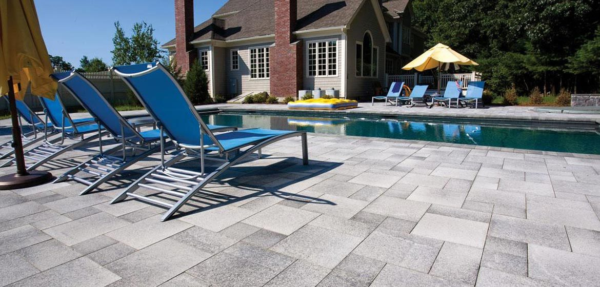 unilock umbriano concrete paver pool deck with aluminum sling chaise lounge chairs