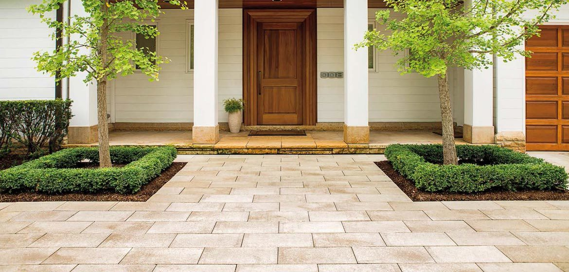 Unilock's Summer Wheat Umbriano concrete paver installed at the entrance to a home with a stained wood front door