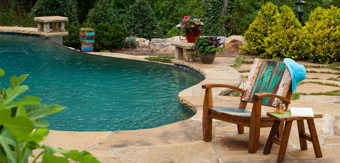 Warehouse 2120's recycled boatwood outdoor lounge chair and side table on an irregular flagstone patio by a beautiful pool with a diving rock