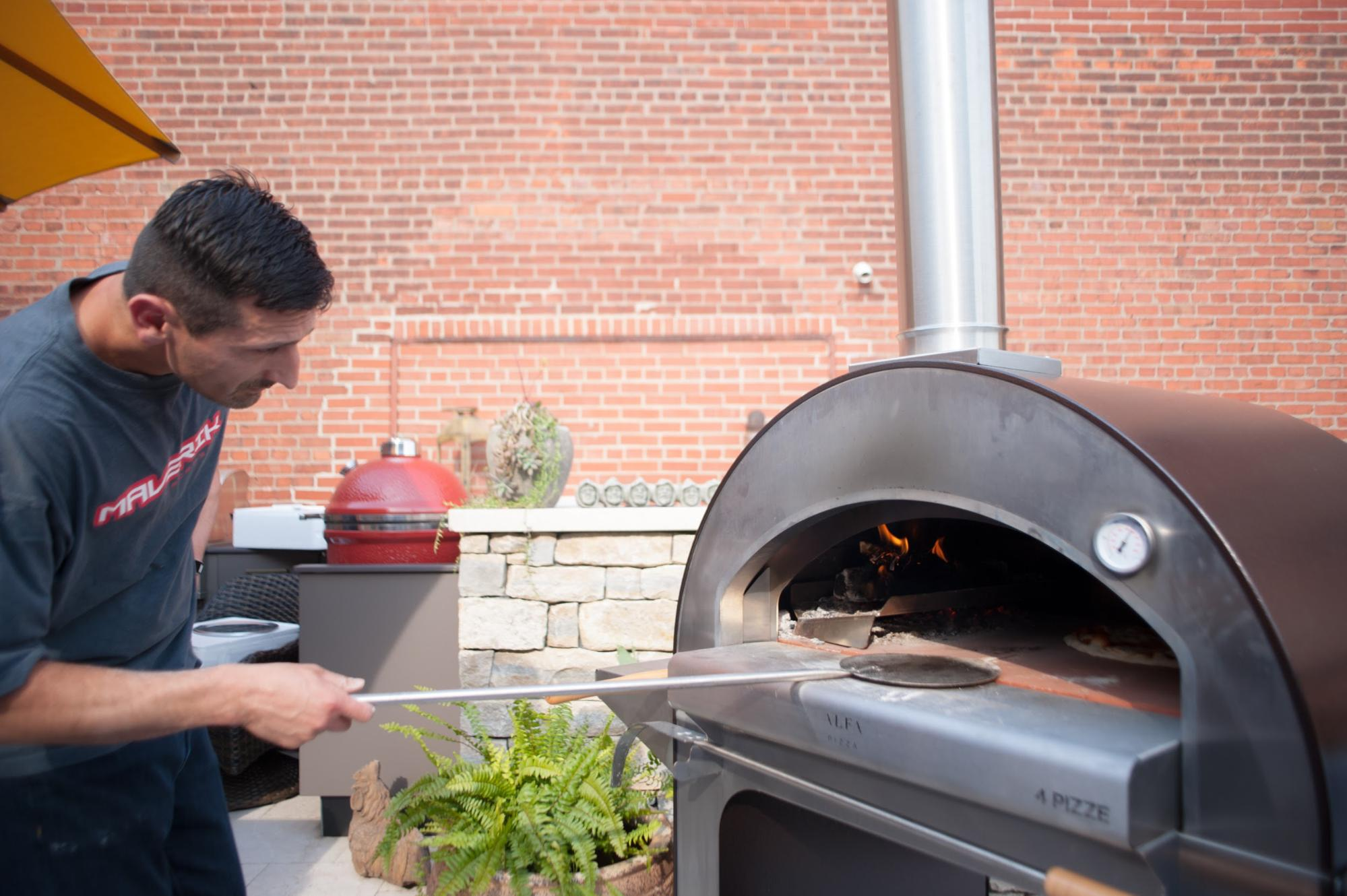 Man tending to pizza in ALFA 4 Pizze oven