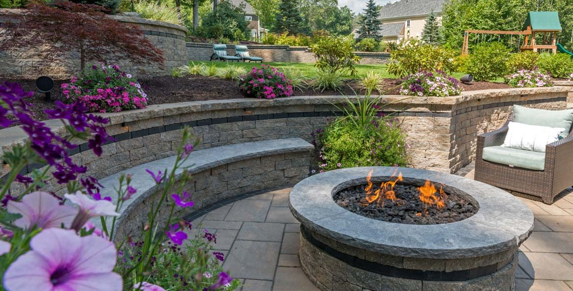 unilock beacon hill flagstone patio with retaining wall and roman stack fire pit