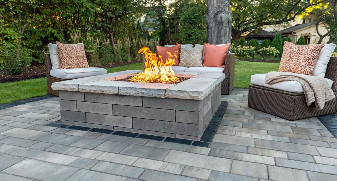 unilock artline pavers surround this lino fire pit with contemporary wicker furniture
